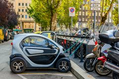 A small electric car on charge. Italy. Free Recharging Station. A small electric car on charge. Milan, Italy. Free Recharging Station Stock Photo
