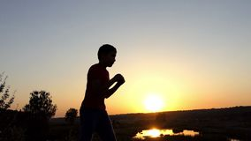 Small boy trains boxing blows on a lake bank at sunset in autumn in slo-mo. A Small Eleven-Year-Old Boy in Pants and a T-Shirt Delivers Boxing Straight, Uppercut stock footage