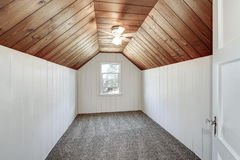 Small empty attic room with wood paneling and vaulted ceiling. Small empty attic room with wood paneling, carpet floor and vaulted ceiling. Northwest, USA Stock Images