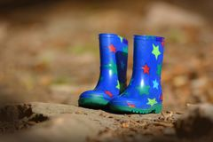 Small blue children rubber boots with colorful stars staning in autum forest surronding stock photos
