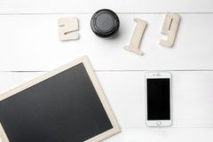Small empty Chalkboard or Blackboard and mobile phone and Cutout wooden digits forming number of New Year 2019 with camera photo stock image