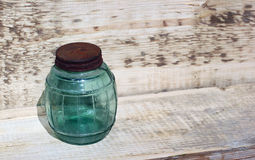 Small empty glass jam jar with rusty metal cover lid. On wooden background Stock Photo