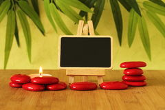 Small empty slate in width to write a message that is posed on an easel with red stones  columns on the ground in zen lifestyle wi. Empty slate in width to write Royalty Free Stock Image