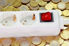 Small Energy Costs. Power strip on euro coins royalty free stock image