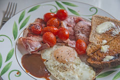 Small English breakfast. Closeup with fried egg, bacon, tomatoes, toast and brown sauce royalty free stock photography