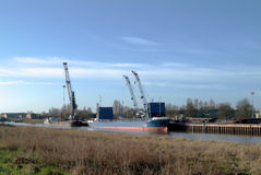 Small English port. Cargo shipping alongside the quay of a small port in England (Sutton Bridge, Lincolnshire), with cranes, blue sky, river royalty free stock image