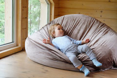 Small European boy lies on a bean bag Royalty Free Stock Photo