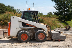 Small excavator Bobcat. At construction site Stock Photo