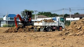 A small excavator filling up a small dump truck. With soil on a construction site on December 21, 2017 in Pakkret in Nonthaburi, neighboring province of Thai stock footage