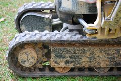 Small excavator& x27;s tracks. A photo taken on a small excavator& x27;s wheels and tracks. It is filled with mud from the construction work it does stock image