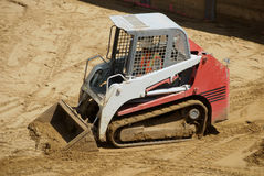 Small excavator or skid loader. A small tracked skid loader crosses a sandy service at a construction site Royalty Free Stock Photos