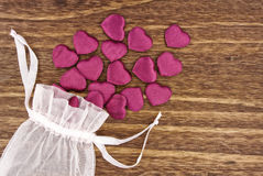 Small Fabric Hearts Spilling Out of a Pouch Royalty Free Stock Images