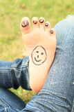 Small faces on toes and sole. Kids bare foot with funny five small faces - smileys on toes and one on sole Royalty Free Stock Image