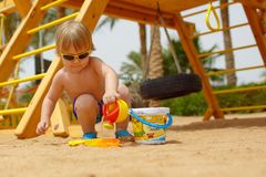 Small fair hair child boy in the playground in hot country royalty free stock photography