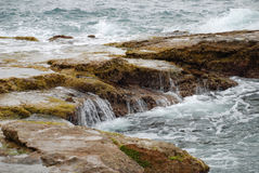 Small falls. Large stones at seacoast, on them roll easy waves Stock Images