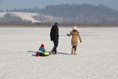 A small family on a frozen lake. Austria, Europe. Royalty Free Stock Images