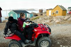 Small family on a quad bike, GREENLAND - September 9, 2012:. Small family on a quad bike which is a popular mode of transport in this is remote village stock photography