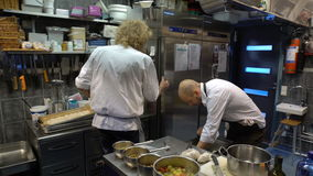 Small family restaurant. Two chefs prepare seafood dishes. HANKO, FINLAND - NOVEMBER 26, 2016: Small family restaurant Pa Kroken . Famous chefs Hans Valimaki stock video footage