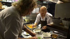 Small family restaurant. Two chefs prepare seafood dishes. HANKO, FINLAND - NOVEMBER 26, 2016: Small family restaurant Pa Kroken . Famous chefs Hans Valimaki stock footage