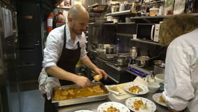 Small family restaurant. Two chefs prepare seafood dishes. stock video