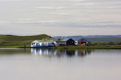 Small farm reflecting in still water on a cloudy day, Myvatn lak Royalty Free Stock Images