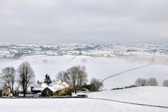 Small Farmhouse in Snow Covered Hills Royalty Free Stock Image
