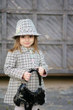 Small fashionable. A small woman of fashion in a checked coat and hat. In the hands of black handbag Royalty Free Stock Photography