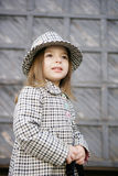 Small fashionable. A small woman of fashion in a checked coat and hat. In the hands of black handbag Royalty Free Stock Photos