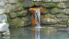 A small faterfall in a stony wall at a forest lake in slo-mo. An exciting view of a small faterfall in a stony wall at a forest lake on a sunny day in summer in stock video footage