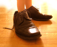 Small feet in big shoes. Child's feet in big black shoes Royalty Free Stock Images