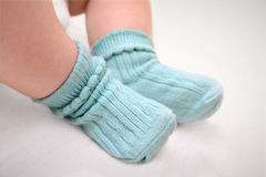 Small feet in socks. Close up of babies feet wearing blue cotton socks Stock Photography