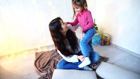 Female sister with youngest girl do hairstyle sitting on floor in room on background of wall with garland and small fir stock video