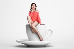 Small female sitting on giant coffee cup; woman on diet, Royalty Free Stock Photos
