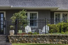 Small fenced garden area outside entrance to stucco house with two adult chairs and one childs chair royalty free stock photography