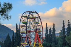 Small ferriswheel among trees. With clouds Stock Photos