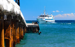 Small ferry approaching a landing on a pier Stock Photos