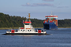 Small ferry and container ship on Kiel Canal Royalty Free Stock Images