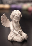 Small figure of an angel. Beoaya small figure of an angel on a dark background Royalty Free Stock Image