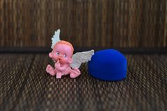 A small figure of an angel sitting on or near a jewelry box close up royalty free stock images