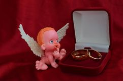 A small figure of an angel sitting near a jewelry box close up on red background stock photography