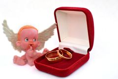 A small figure of an angel sitting near a jewelry box with two golden wedding rings isolated on white. The concept of thoughts of a gift royalty free stock photo