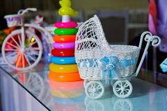 A small figure of an jewelry box stroller close up . Toy for decoration pink stroller stock photo
