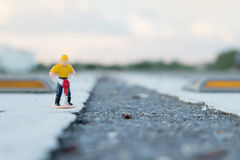 Small figure of a man digging street Royalty Free Stock Photos