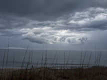 Small Figure on the Shore Below Threatening Sky Stock Image