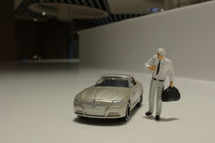 Small figure with the toy car Royalty Free Stock Images