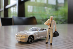 Small figure with the toy sport car Royalty Free Stock Photo