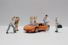 Small figure with the toy sport car Royalty Free Stock Photos