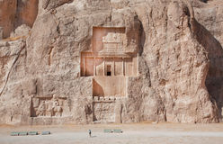 Small figure of woman walking past the historical monuments of Naqsh-e Rustam Royalty Free Stock Images