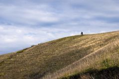 Small figures of people on the hillside Stock Images