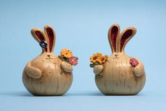 Small figures of two hares with flowers on a blue background royalty free stock photos